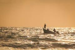 站立在小船的渔夫在海日落 免版税库存图片