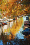 站立在小船附近和在运河的反射 免版税库存图片