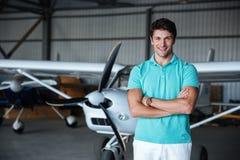 站立在小飞机附近的快乐的年轻人 免版税库存照片