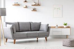 站立在居住的ro的白色碗柜旁边的简单,灰色沙发 库存照片