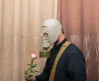 站立在屋子里和举行ros的防毒面具的人 免版税库存图片