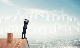 站立在屋顶和看在双筒望远镜的商人 混杂我 免版税库存照片
