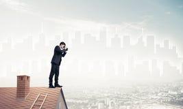 站立在屋顶和看在双筒望远镜的商人 混杂我 图库摄影