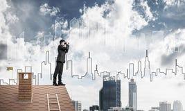 站立在屋顶和看在双筒望远镜的商人 混杂我 库存图片