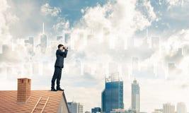 站立在屋顶和看在双筒望远镜的商人 混杂我 免版税图库摄影