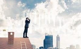 站立在屋顶和看在双筒望远镜的商人 混杂我 库存照片