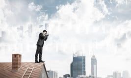 站立在屋顶和看在双筒望远镜的商人 混杂我 免版税库存图片