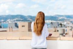 站立在屋顶大阳台的妇女 免版税库存照片