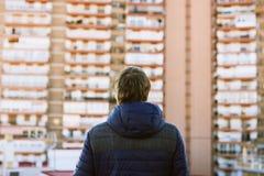 站立在屋顶大阳台的白肤金发的人,回到照相机lookin 免版税库存图片