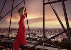 站立在屋顶边缘的典雅的夫人 免版税库存图片