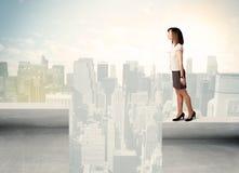 站立在屋顶边缘的女实业家 库存图片