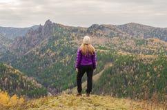 站立在山、山的看法和秋天森林的一件淡紫色夹克的一个女孩 免版税库存图片