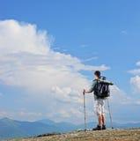 站立在山上面的男性远足者 免版税库存照片