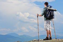 站立在山上面的男性远足者 免版税图库摄影