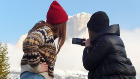 站立在山前面和拍照片的它的两名年轻旅行的妇女 影视素材