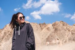 站立在山和蓝天背景前面的一个美丽的亚裔妇女游人 免版税库存图片