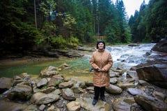 站立在山小河附近的愉快的年长妇女 免版税库存图片