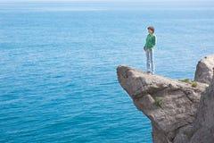 站立在山峭壁a边缘的年轻亭亭玉立的孤独的妇女  免版税库存照片