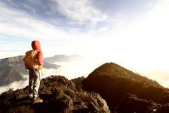 站立在山峰的妇女远足者 库存图片