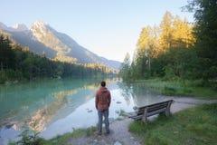 站立在山湖附近的人 免版税库存图片