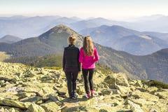 站立在山的两个女孩远足者享受山景 免版税库存照片