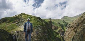 站立在山的峭壁顶部和享受自然,背面图的看法年轻旅客人 库存照片
