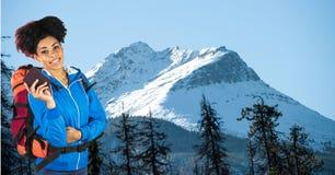 站立在山的行家运载的背包和日志 免版税图库摄影