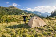 站立在山的远足者近的旅游帐篷 免版税库存图片