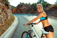 站立在山路的一辆自行车附近的妇女骑自行车者 免版税图库摄影