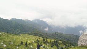 站立在山边缘和观看在绿色山谷寄生虫视图的旅游妇女 股票视频