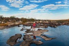 站立在岩石之间的河的少妇 库存图片
