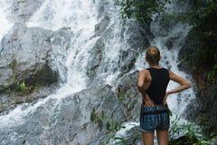 站立在岩石和查寻在瀑布附近的白肤金发的妇女 免版税图库摄影