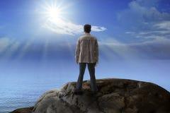 站立在岩石山和看对太阳的年轻人 免版税库存照片