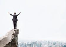 站立在岩石山边缘的年轻商人  免版税图库摄影