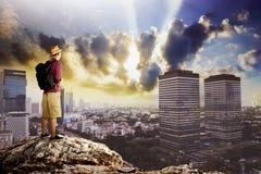 站立在岩石的上面的年轻旅客 库存图片