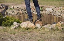 站立在岩石的人脚 库存照片