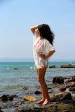 站立在岩石的女孩在海附近 库存照片