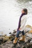站立在岩石的妇女在河旁边 库存图片