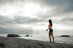 站立在岩石的妇女在Bakovern海滩,开普敦的日落 免版税库存图片
