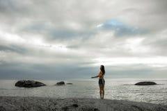 站立在岩石的妇女在Bakovern海滩,开普敦的日落 库存照片