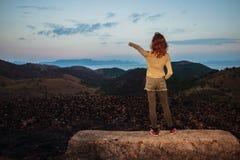 站立在岩石的妇女指向 免版税库存照片