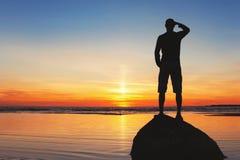 站立在岩石的年轻人剪影在日落背景 免版税库存照片