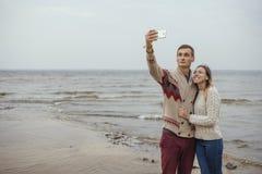 站立在岩石的愉快的周道的夫妇在海huggin附近靠岸 免版税库存图片