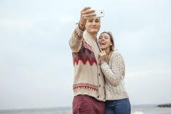 站立在岩石的愉快的周道的夫妇在海huggin附近靠岸 库存图片