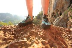 站立在岩石的攀岩运动员腿 免版税库存照片