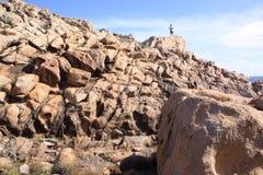 站立在岩石的游人在Yallingup海滩在西澳州 免版税库存照片