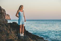 站立在岩石的年轻白肤金发的妇女在海,阿拉尼亚,土耳其旁边 库存照片