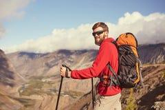 站立在峡谷边缘的英俊的年轻有胡子的男性远足者看  库存照片