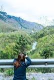 站立在峭壁和拍摄谷的照片与河的女孩 做与智能手机的红色头图片对塔拉 免版税库存照片