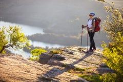 站立在峭壁的女性远足者 免版税库存图片